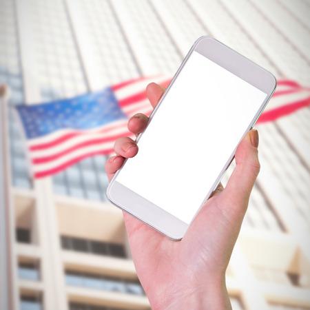 sky scraper: Hand holding smartphone against american flag against sky scraper Stock Photo
