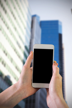 mobile phone screen: Hand holding smartphone against low angle view of skyscrapers