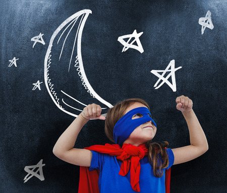 standing up: Masked girl pretending to be superhero against black background