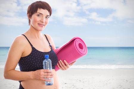 waters: Pregnant woman holding water bottle and exercise mat against waters edge at the beach