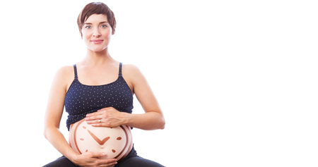 against the clock: Portrait of happy pregnant woman holding belly against clock Stock Photo
