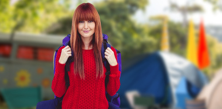 campsite: Smiling hipster woman with a travel bag taking selfie against empty campsite at music festival