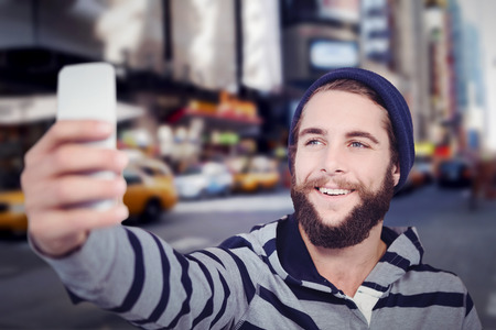 hooded shirt: Happy hipster with hooded shirt taking selfie against blurry new york street Stock Photo