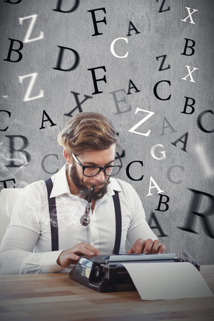 smoking pipe: Hipster smoking pipe while working on typewriter against white and grey background Stock Photo
