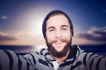 hooded shirt: Portrait of happy hipster with hooded shirt against scenic view of sea against sky Stock Photo