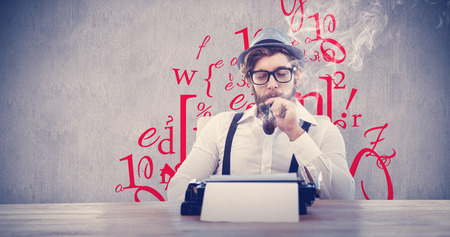 smoking pipe: Hipster smoking pipe while sitting looking at typewriter against white and grey background Stock Photo