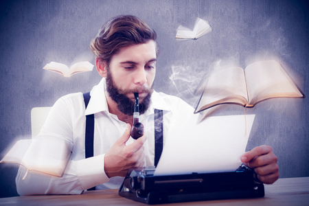 smoking pipe: Hipster with smoking pipe working on typewriter against white and grey background Stock Photo
