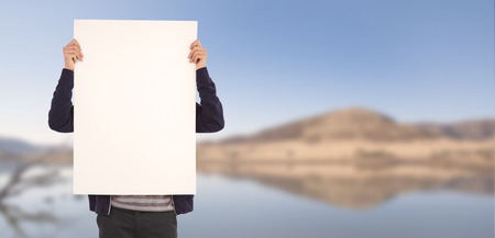 lake front: Man showing billboard in front of face against lake Stock Photo