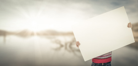 big behind: Hipster woman behind a big white card against lake Stock Photo