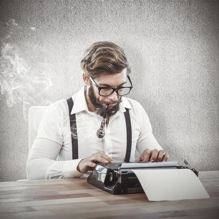 cool guy: Hipster smoking pipe while working on typewriter against grey wall