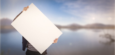sign in: Man holding billboard in front of face against lake