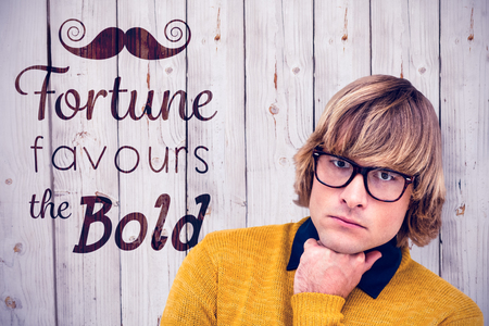 favours: Portrait of thoughtful hipster businessman with hand on chin against wooden background