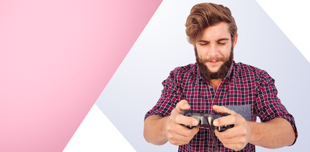 playing video game: Hipster playing video game against pink background Stock Photo