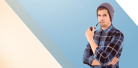 smoking pipe: Portrait of hipster holding smoking pipe against blue vignette background Stock Photo