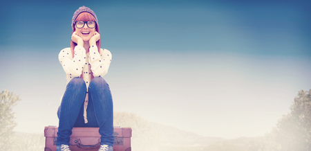 casual clothing: Smiling hipster woman sitting on suitcase  against mountain trail