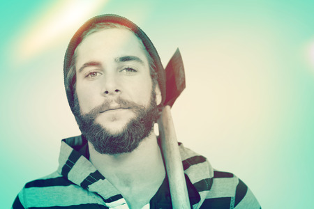 hooded shirt: Close-up portrait of hipster with hooded shirt holding axe against blue vignette background