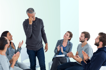 standing up: Rehab group applauding delighted man standing up against bright blue Stock Photo