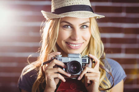 vintage: Blonde woman taking picture on brick wall LANG_EVOIMAGES