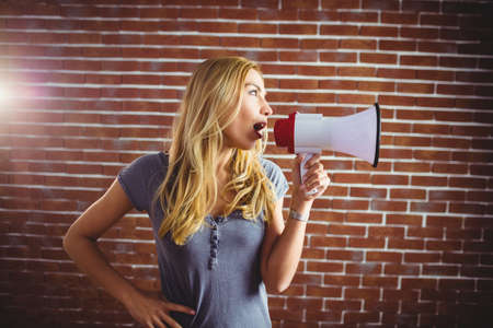 yelling: Woman yelling through megaphone on brick wall LANG_EVOIMAGES
