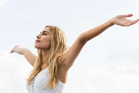 outstretched: Beautiful blonde woman with arms outstretched in the coastline