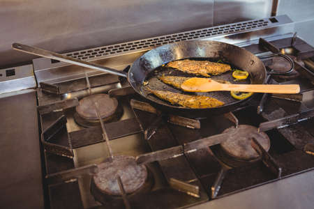 commercial kitchen: Fish frying in a pan in a commercial kitchen