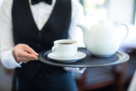 stand teapot: Waitress with tray of tea in a commercial kitchen