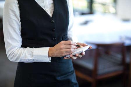 20s waitress: Waitress taking an order in a restaurant