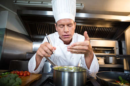 wafting: Happy chef smelling his dish in a commercial kitchen LANG_EVOIMAGES
