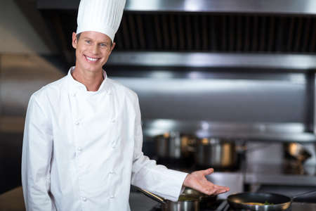 hotel staff: Happy chef smiling at camera in a commercial kitchen