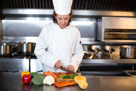commercial kitchen: Chef slicing vegetables on wooden board in a commercial kitchen