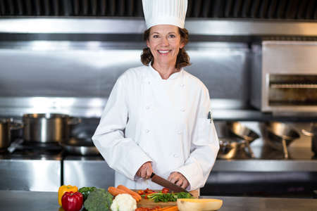 hotel staff: Chef slicing vegetables on wooden board in a commercial kitchen