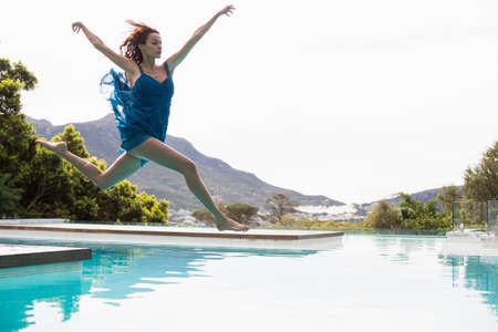 maxi dress: Elegant woman diving in the pool on a summers day