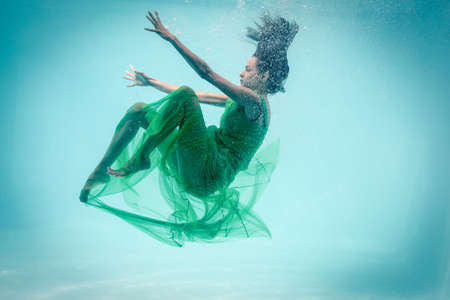 maxi dress: Brunette in evening gown swimming in pool underwater