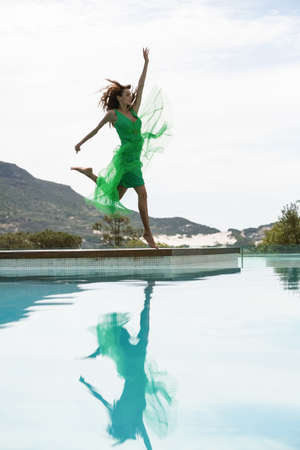 summers: Elegant woman dancing by the pool on a summers day
