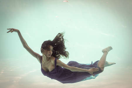 clothed: Brunette in evening gown swimming in pool underwater