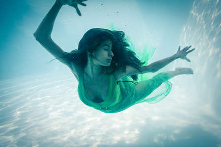 evening gown: Brunette in evening gown swimming in pool underwater