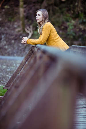 leaning by barrier: Pretty woman leaning on a barrier LANG_EVOIMAGES
