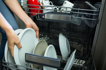 emptying: Pretty blonde woman emptying the dishwasher in the kitchen