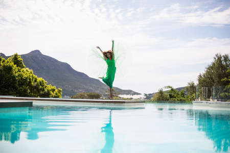 maxi dress: Elegant woman dancing by the pool on a summers day