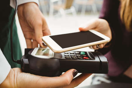 paying: Woman paying with mobile phone in cafe LANG_EVOIMAGES