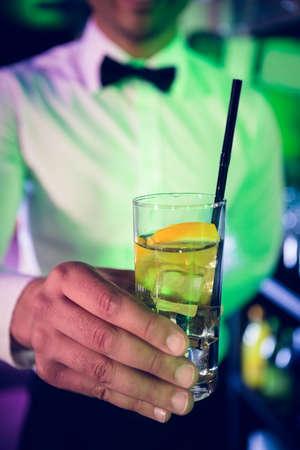 bar counter: Bartender serving glass of gin at bar counter in bar
