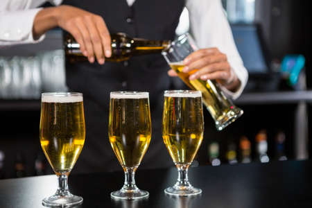 bartending: Three glasses of beer ready to serve on bar counter while bartender preparing a drink in background