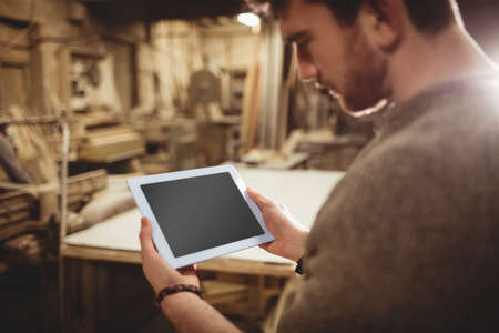 carpenter's bench: Happy carpenter using his tablet in a dusty workshop
