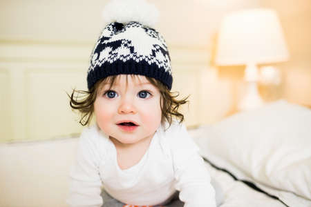 beanie: Cute baby wearing a beanie on the bed LANG_EVOIMAGES
