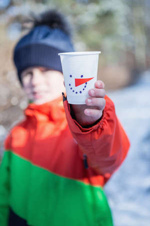 people: Cute boy showing cup on a beautiful snowy day LANG_EVOIMAGES