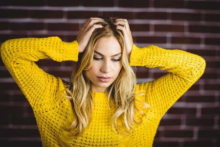 dreariness: Beautiful blonde woman holding her head on brick wall