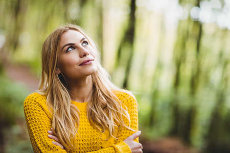 adventuring: Beautiful blonde woman day dreaming in the woods