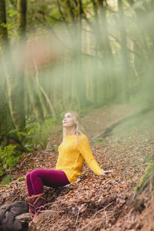 adventuring: Beautiful blonde woman sitting on the ground in the woods