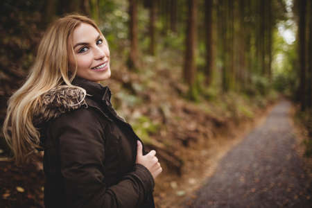 adventuring: Beautiful blonde woman walking on road surrounded by forest