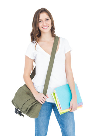 shoulder bag: Portrait of happy female college student holding books and shoulder bag while standing on white background